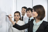 Chinese business woman writing on whiteboard. — Stock Photo