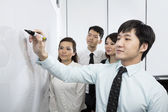 Chinese Business man writing on whiteboard — Stock Photo