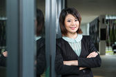 Happy Chinese Business woman standing by window. — Stock Photo