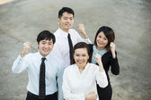 Chinese business team looking up & cheering. — Stock Photo