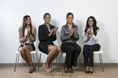 Indian business woman sitting on a row of chairs clapping — Stock Photo