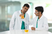 Two Indian scientists analyzing solution. — Stock Photo