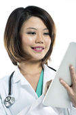 Chinese lady doctor reading her digital tablet. — Stock Photo