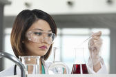 Woman scientist analyzing a solution. — Stock Photo