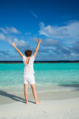 Happy woman standing on tropical beach. — Stock Photo