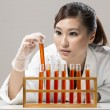 Chinese Woman scientist analyzing a solution. — Stock Photo