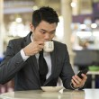 Businessman in a cafe drinking coffee — Stock Photo #27023327