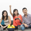 Young Chinese friends playing video games at home — Stock Photo