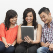 Chinese friends hanging out together using Digital Tablet — Foto de Stock
