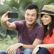 Stock Photo: Chinese Couple taking photo of themselves with smartphone