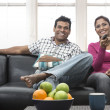 Happy Indian couple on the sofa — Stock Photo #27025667