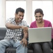 Young Indian couple the couch with laptop — Stock Photo #27025719