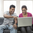 Young Indian couple the couch with laptop — Stock Photo