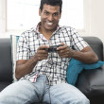 Indian man sitting on sofa playing video games — Stock Photo