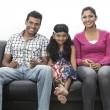 Photo: Parents and child relaxing at home on sofa.