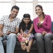 Parents and child relaxing at home on sofa. — Stockfoto #27025963