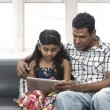 图库照片: Indian father and daughter using digital tablet together.