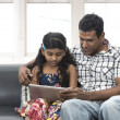 Foto Stock: Indian father and daughter using digital tablet together.