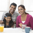 Indian family helping their child with her study work — Stock Photo