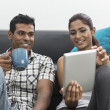 Young Indian couple using a digital tablet — Stock Photo #27026317