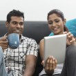 Stock Photo: Young Indian couple using a digital tablet