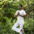 Indian man doing yoga exercise in a forest — Stock Photo