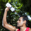 Indian man pouring water on himself while exercising — Stock Photo
