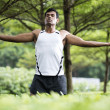 Indian man doing yoga exercise in park — Stock Photo #27027869