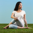 Young Chinese woman sitting meditating on grass — Stock Photo
