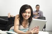 快乐的亚洲女人在家中使用数字平板电脑 — 图库照片
