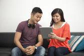 Giovane coppia cinese usando una tavoletta digitale — Foto Stock