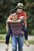 Portrait of a Chinese man giving a piggyback to his girlfriend — Stock Photo