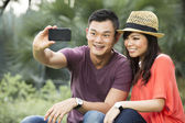 Chinese Couple taking photo of themselves with smartphone — Stock Photo