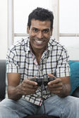 Indian man sitting on sofa playing video games — Stock Photo