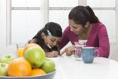 Indian mum helping child with homework — Stock Photo