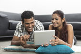 Young Indian couple using a digital tablet — Stock Photo