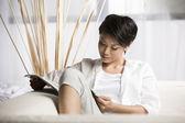 Donna cinese leggendo una rivista a casa — Foto Stock
