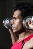 Athletic Indian man exercising with dumbbells — Stock Photo