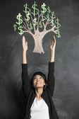 Asian woman reaching for chalk money tree drawn on blackboard. — Stock Photo