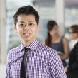 Asian business man standing in office — Stock Photo
