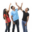 Group of happy Indian friends pointing upwards. — Stock Photo