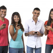 Group of young Indian friends using their smartphones. — Stock Photo