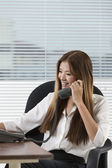Young Asian woman at work in an office. — Stock Photo