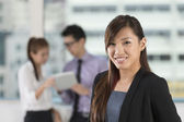 Asian business woman standing in office — Stock Photo
