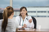 Asian doctor talking with female patient — Stock Photo