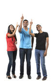 Group of happy Indian friends pointing upwards. — Foto Stock