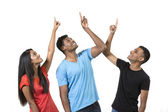 Group of happy Indian friends pointing upwards. — Foto de Stock