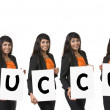 Indian businesswoman holding a white banner spelling word succes — Stock Photo