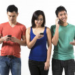 Group of young Chinese friends using their smartphones. — Foto de Stock