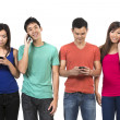 Group of young Chinese friends using their smartphones. — Stockfoto